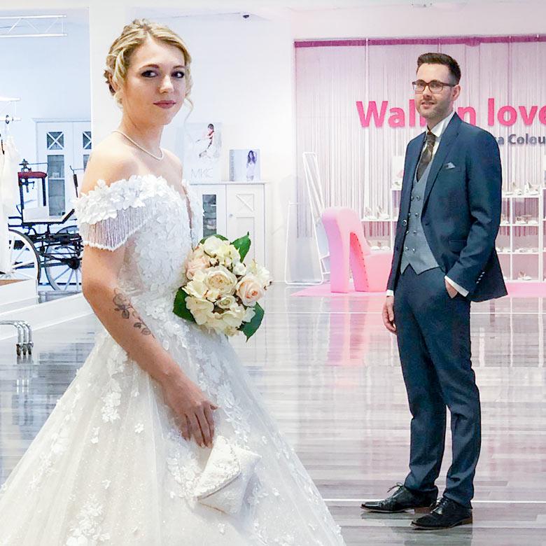 Ein Paar, das in die Kamera schaut und Hochzeitskleidung trägt