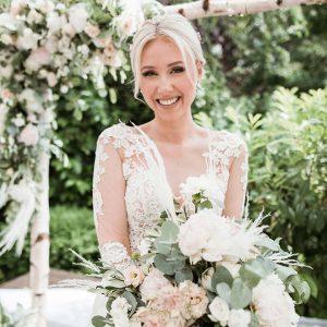 Just Celebrate | Braut lächelnd mit Blumenstrauß